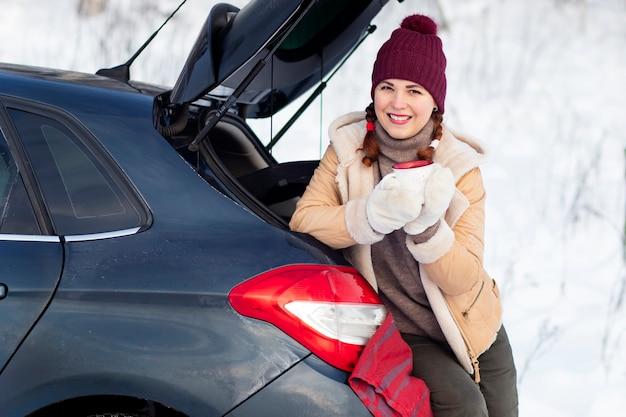 居心地の良い女性が微笑む、暖かい冬の服を着た女性がマグカップを持って、車のトランクに座って微笑む。休暇、車での旅行、雪の寒さ。