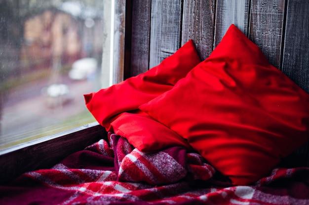 침대보와 빨간 베개가 놓인 아늑한 나무 창틀