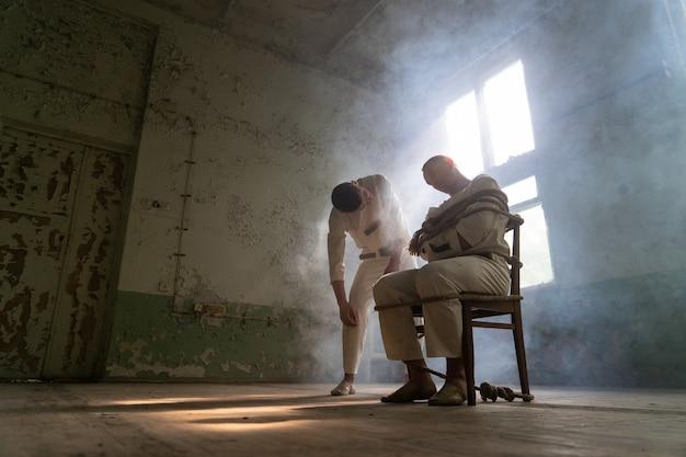 구속복을 입은 미친 남자는 버려진 낡은 클리닉의 의자에 묶여 있고 다른 미친 남자는 관심을 가지고 다가오고 있습니다.