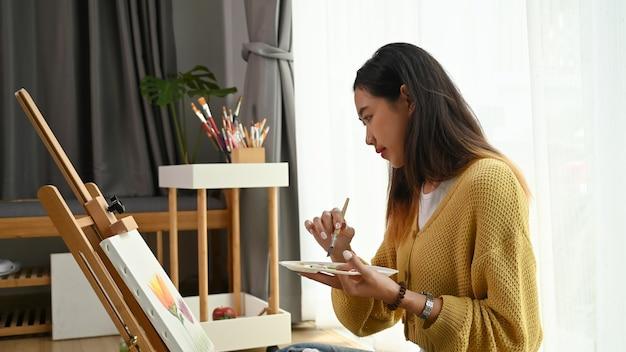 Творческая красивая художница на пенсии рисует в своей мастерской