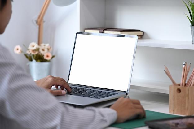 Креативный дизайнер человек работает над ноутбуком с пустым экраном в офисе.