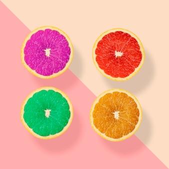 パステルカラーの背景に創造的な幻想的な4つのオレンジ色の果物、紫赤緑とオレンジ色の果物