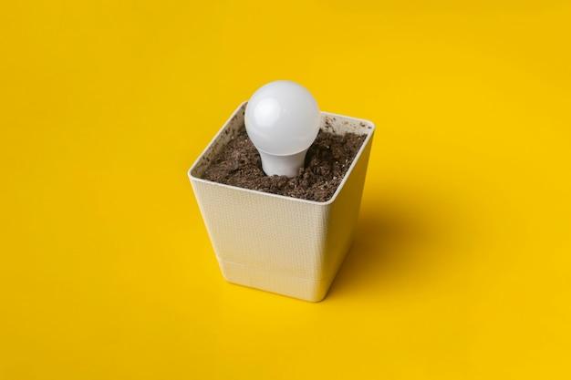 色の表面にコピースペースがある土と鍋の電球の創造的なアイデア