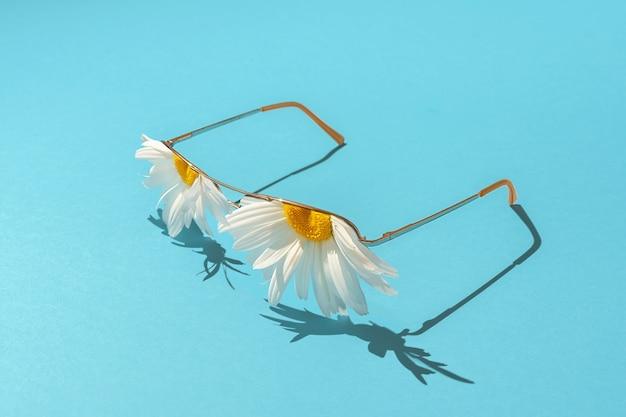 創造的な夏休みのコンセプト。青い背景にレンズの代わりにカモミールが付いた日焼け止めサングラス。