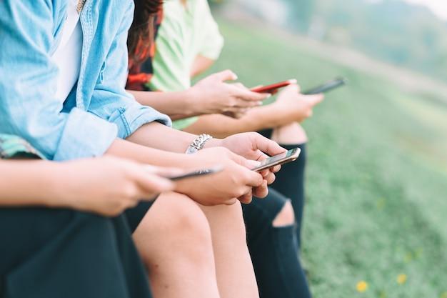 잘린 a 그룹 아시아 친구들이 스마트 폰을 사용하여 공원에서 채팅을하고 있습니다.