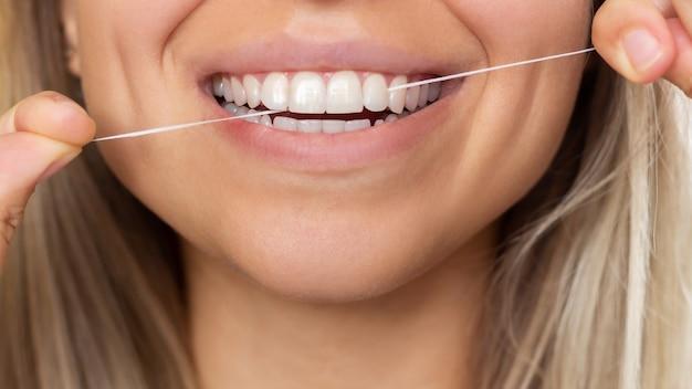 彼女の歯をフロスする若い美しい女性のトリミングされたショットクローズアップ歯科の概念
