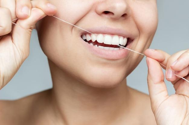 Обрезанный снимок молодой женщины, чистящей зубы зубной нитью, гигиена полости рта, утренний уход за зубами