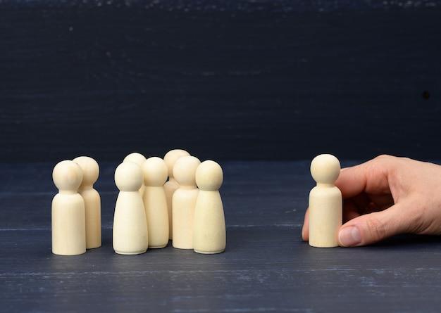 Толпа деревянных фигурок напротив руки держит одну фигуру