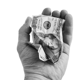 しわくちゃの百ドルの現金札を手に。白い壁に隔離。