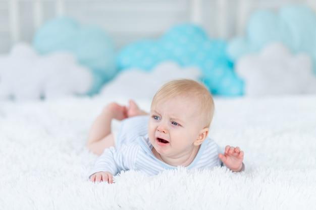 Плачущий мальчик на кровати ложится спать или просыпается утром