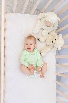 침실에 이빨이 있는 유아용 침대에서 우는 아기.