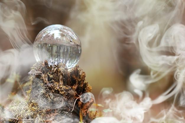 Хрустальный шар в дыму. волшебный аксессуар в лесу на пне. ритуальный шар ведьм и колдунов на старом гнилом пне, покрытом мхом.