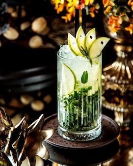 Хрустальный бокал напитка мохито, украшенный кусочками зеленого яблока