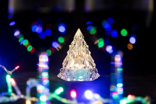 クリスタルの輝くクリスマスツリーが、輝く花輪に囲まれたぼやけた2つのワイングラスの後ろに立っています。クローズアップ、ソフトフォーカス...