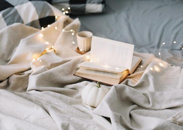 Чашка и книга завтрак в постели с серыми простынями и подушками ленивые выходные милый дом
