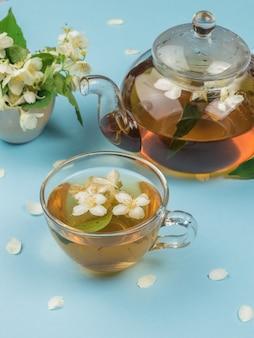 青い背景に花のお茶とカップとガラスのティーポット