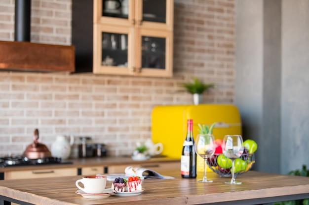 皿の上のカップとケーキ、ワイングラス、ワインとフルーツのボトルは、キッチンのインテリアのテーブルの上に立っています