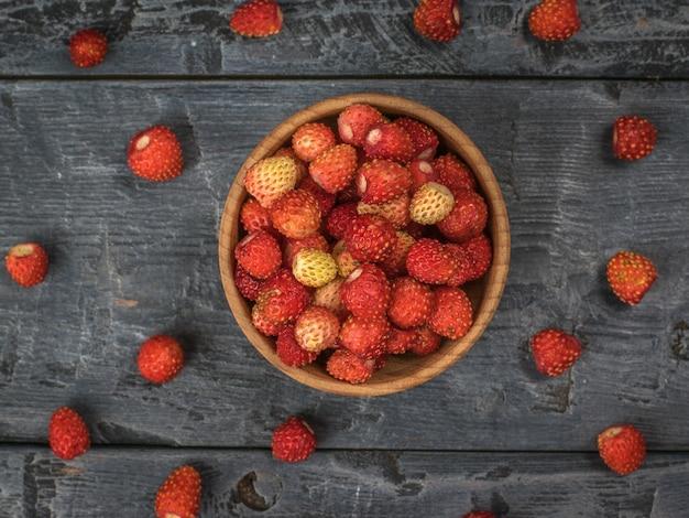 カップと木製のテーブルに散らばった野生のイチゴ。新鮮な作物。