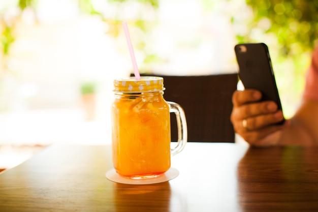 木製のテーブルの上にカクテルストローと新鮮なオレンジジュースでいっぱいのカップ。男はモバイル写真をやっています