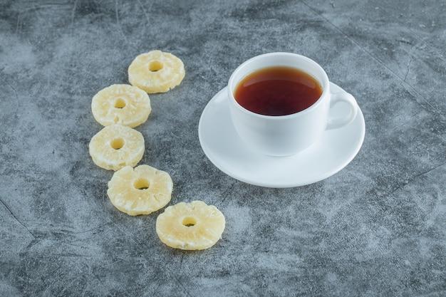 Чашка ароматного чая с сушеными ананасами.