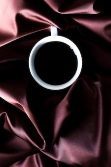 Чашка ароматного черного кофе эспрессо на фоне шелковой ткани шоколадного оттенка