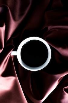 チョコレート色合いのシルク生地の背景に芳香の黒いエスプレッソコーヒーのカップ