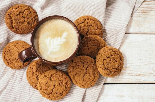 オートミールクッキーとテーブルクロスと木製のテーブルと芳香族コーヒーカプチーノのカップ