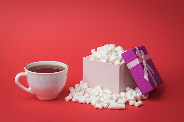 Чашка черного кофе и коробка зефира. сладкое угощение.