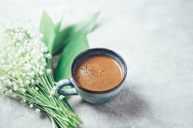 Чашка черного кофе на белом бетонном столе и букет весенних белых цветов ландыша