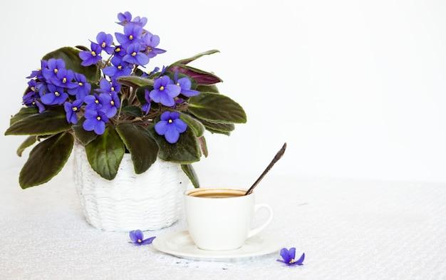 테이블에 블랙 커피 한 잔과 공간 사본이 있는 수제 보라색 꽃.