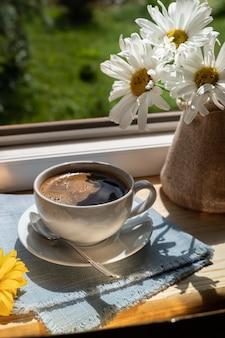 Чашка черного кофе на подоконнике под лучами солнца, рядом с красивыми цветами, вертикальный снимок.