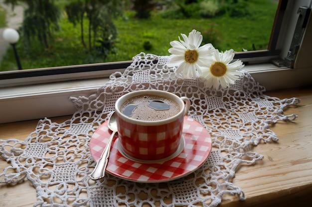 Чашка черного кофе на подоконнике под лучами солнца.