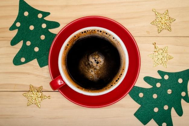 木製の背景にクリスマスの装飾が施されたブラックコーヒーのカップ。