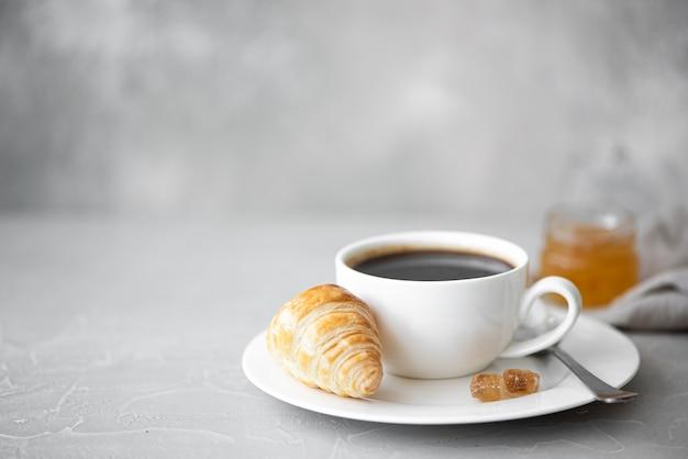 クロワッサンとジャムとブラックコーヒーのカップ