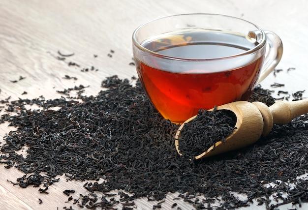 木製のテーブルの上に紅茶と乾燥紅茶の葉のカップ