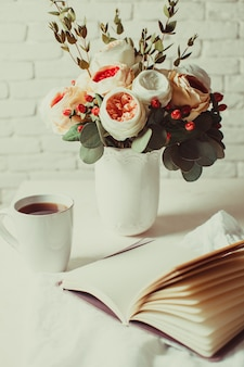 テーブルの上に紅茶、ノート、美しい花を一杯。一日の計画のための朝のインスピレーション