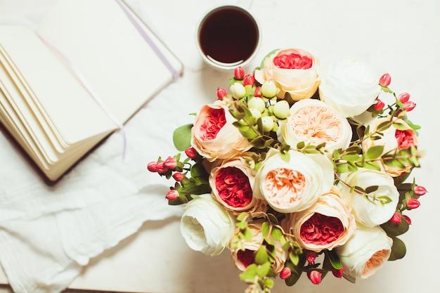 一杯の紅茶、ノート、テーブルの上の美しい花、上面図。創造性へのインスピレーションの概念