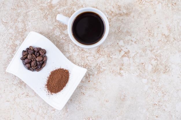 派手な大皿にコーヒー豆と挽いたコーヒーパウダーの横にある淹れたてのコーヒーのカップ