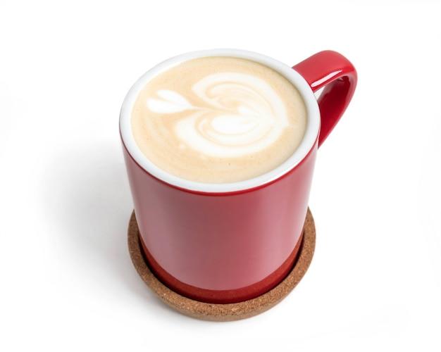 白い背景で隔離の赤いカップのカプチーノのカップ