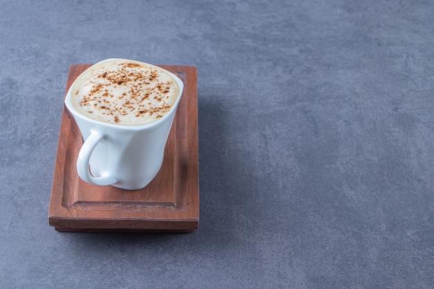 Чашка капучино на деревянной тарелке рядом с нарезанным лимоном на синем фоне.