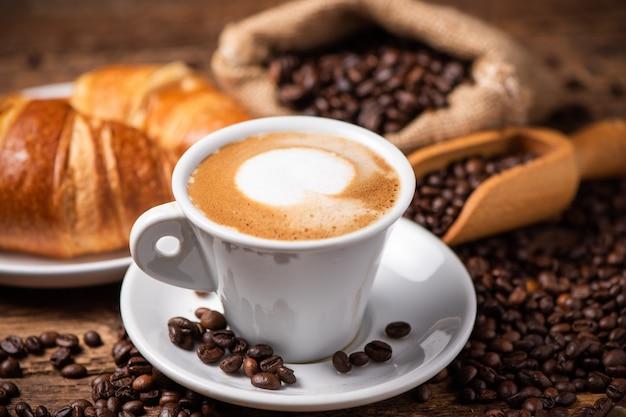 背景としてコーヒー豆とカプチーノのカップをクローズアップ