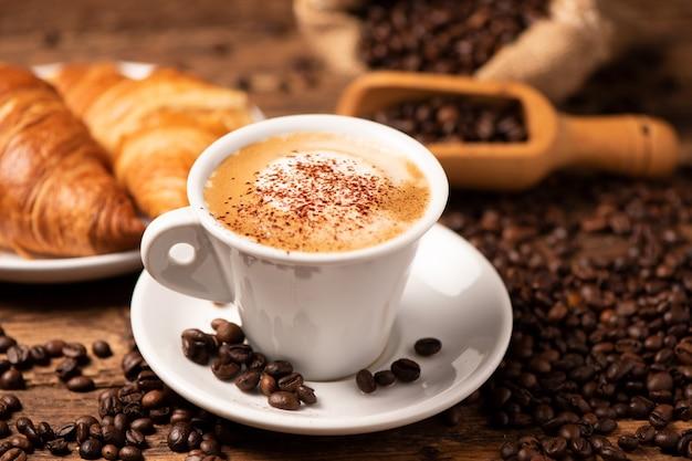 배경으로 커피 콩을 넣은 카푸치노 한 잔