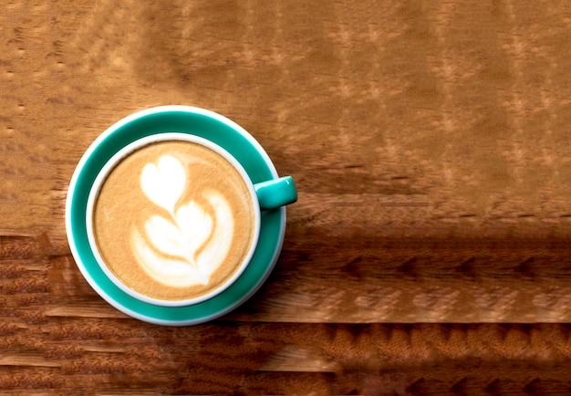 木製の背景にラテアートとカプチーノのカップ。美しい泡、ミントセラミックカップ。フラットレイ。
