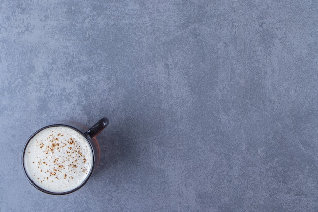 青いテーブルの上に、ミルクとカプチーノのカップ。