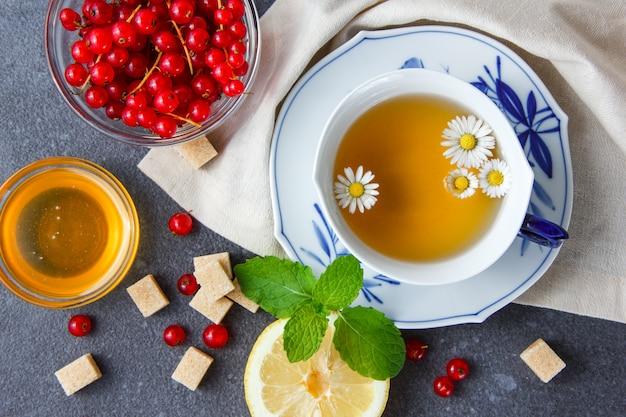 Чашка ромашкового чая с сахаром, листья, лимон, красная смородина в миску сверху