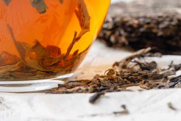 Чашка китайского чая рядом с большим кусочком пуэр