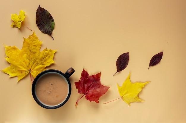 Чашка какао и осенних листьев на бежевом