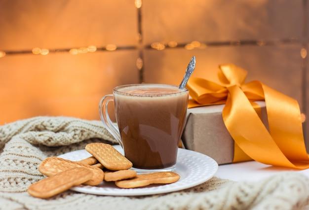 Чашка какао и печенья на белой тарелке на белом столе и подарок с золотой лентой