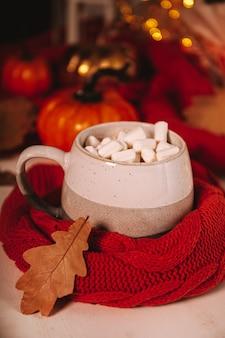 Чашка какао с зефиром и осенними листьями в руках атмосферная осенняя картина с