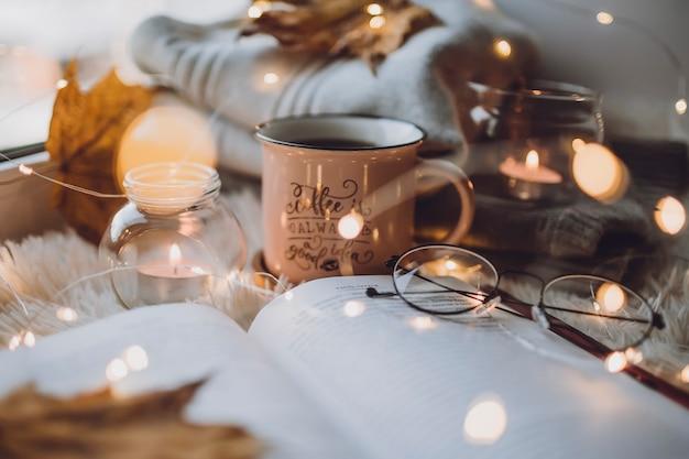 一杯のコーヒー、白い毛布の本、ろうそく、グラス。